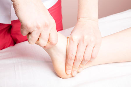 Elementary age girls foot joint being manipulated by an osteopath - an alternative medicine treatment