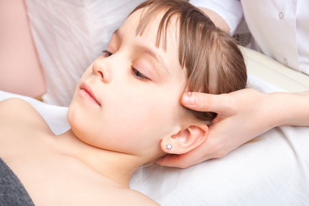 Elementary age girls head being manipulated by an osteopath - an alternative medicine treatment