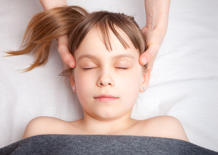 Elementary age girl's head being manipulated by an osteopath - an alternative medicine treatment