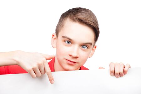 Cute teenager boy wearing red polo shirt  pointing his finger on blank white board or banner. Isolated on white background photo