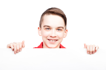 Cute teenager boy looking out from blank white board or banner that he holds in his hands Isolated on white background photo