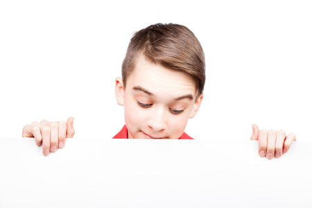 Cute teenager boy looking down at blank white board or banner that he holds in his hands Isolated on white background photo