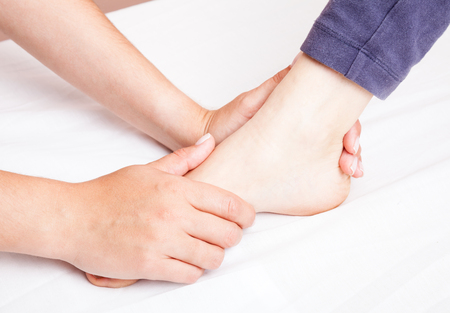 Young woman's foot joint being manipulated by an osteopath - an alternative medicine treatment photo