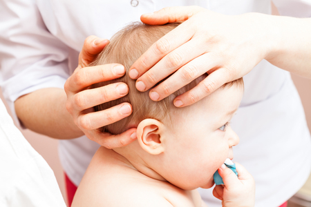 rehabilitation: Seven month baby girls head being manipulated by an osteopath - an alternative medicine treatment