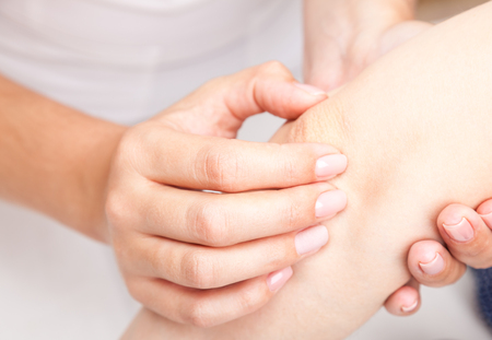 Young woman's elbow joint being manipulated by osteopathic manual therapist or physician
