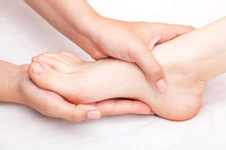Young womans foot joint being manipulated by osteopathic manual therapist or physician Stock Photo