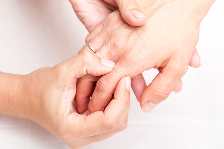 Young womans finger being manipulated by osteopathic manual therapist or physician Stock Photo