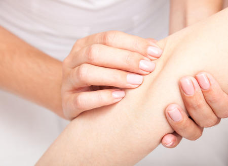 Young womans elbow joint being manipulated by osteopathic manual therapist or physician Stock Photo