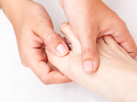 Young womans foot finger being manipulated by osteopathic manual therapist or physician