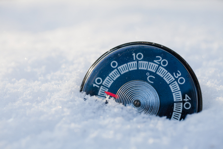 Vintage thermometer with celsius scale showing sub-zero temperature placed in a fresh snow in winter Stock Photo