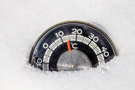Roung thermometer with celsius scale placed in a snow showing high temperature — warm winter weather global warming climate change concept