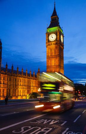 Double Decker bus moves along illuminated Elizabeth Tower aka Big Ben on the Westminster Bridge  at twilight