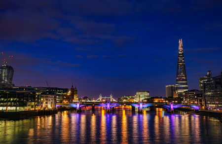 London skyline with illuminated Southwark Bridge over the River Thames and The Shard skyscraper at night