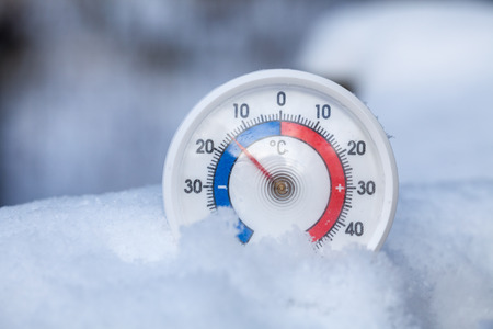 Thermometer with celsius scale placed in a fresh snow showing sub-zero temperature minus fifteen degree a cold winter weather concept Stok Fotoğraf