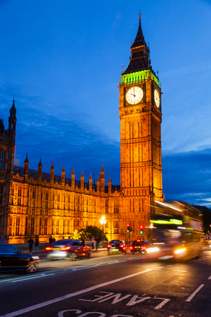 London night traffic scene with Doubledecker bus moves along the Westminster Bridge and  Elizabeth Tower or Big Ben in background Stock Photo