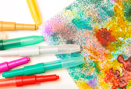 Color marker pens with childs drawing on a table art creativity background