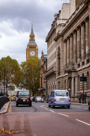 LONDON, UK - OCTOBER 29, 2012: Taxicabs move along the Great George Street with Elizabeth Tower aka Big Ben seeng in background