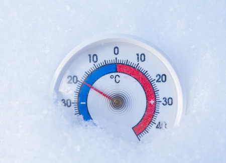 Thermometer with celsius scale placed in a fresh snow showing sub-zero temperature minus 19 degree - cold winter weather concept