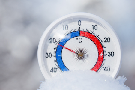 Thermometer with celsius scale placed in a fresh snow showing sub-zero temperature minus 21 degree - cold winter weather concept Stock Photo