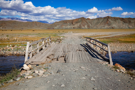 Worn out wooden bridge on a dirt road at Altai Mountains, Western Mongolia