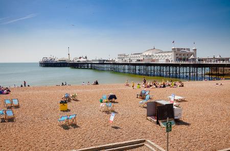 BRIGHTON, UK - JUN 5, 2013: Holidayers enjoying good summer weather at shingle beach near the Brighton Palace Pier