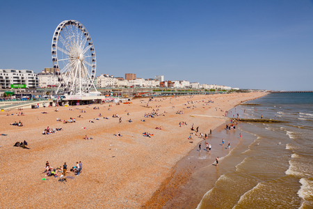 BRIGHTON, UK - JUN 5, 2013:View along the  Brighton Beachfront with the Ferris Wheel promenade and vacationer on shingle beach pictured from the Brighton Palace Pier on a sunny summer day