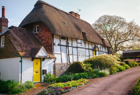 A Typical Traditional English Country Thatched Cottage Decorated With Plants And Blooming Flowers In Rural Southern