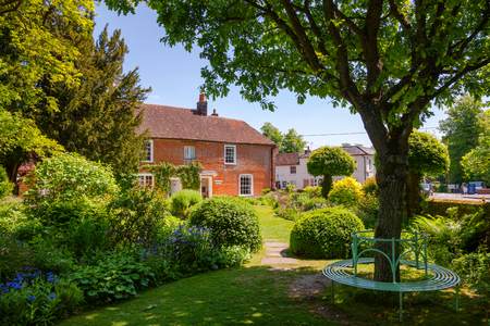 CHAWTON, UK - JUN 8, 2013: Round bench at formal garden of Chawton Cottage, an independent museum of novelist Jane Austen