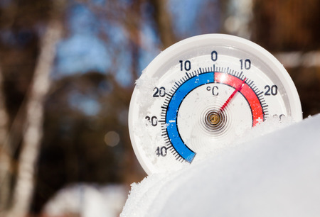Thermometer with celsius scale in melting snow showing plus 12 degree temperature warm spring weather or global warming concept Stock Photo