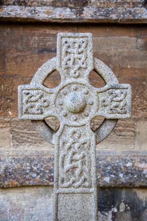 Croce celtica di pietra scolpita un cortile della chiesa, Inghilterra, Regno Unito Archivio Fotografico - 98846451