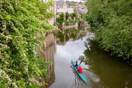 Two women kayaking down the River Avon (Bristol Avon) along scenic Bradford-on-Avon, a town and civil parish in West Wiltshire, Southwest England, UK Stock Photo