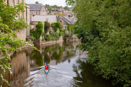 BRADFORD-ON-AVON, UK - JUN 12, 2013: Two women kayaking down the River Avon (Bristol Avon) along old town buildings