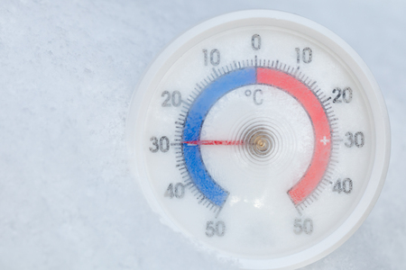 Thermometer with celsius scale placed in a fresh snow showing sub-zero temperature minus 30 degree - extreme cold winter weather concept Archivio Fotografico