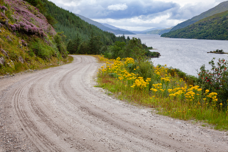 Winding dirt road along the Loch Shiel shore, a National Scenic Area in  Lochaber, Highland, Scotland, UK