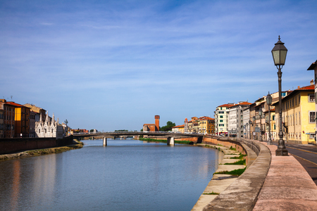 Pisa cityscape with medieval waterfront buldings and Pisan Gothic Santa Maria della Spina church on Arno River embankment, Tuscany, Italy