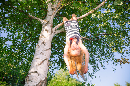 Low angle view of happy girl hanging  upside down from a birch tree looking at camera enjoying summertime Banco de Imagens