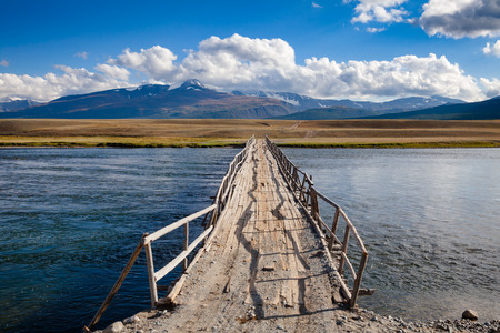 Shabby wooden bridge over a river with distant mountain range in background, Altai Mountains, Western Mongolia