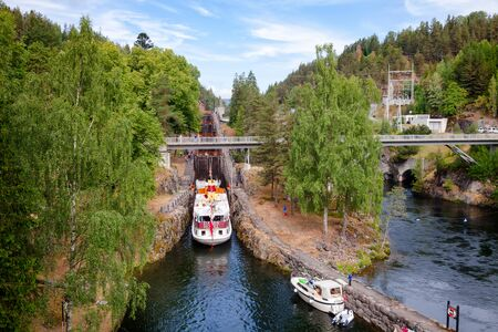 ULEFOSS, NORWAY - JULY 18, 2018: M/S Henrik Ibsen ferry boat entering lock chamber at the Vrangfoss staircase locks during a unique historical boat trip through spectacular Norwegian nature by the Telemark Canal Sajtókép