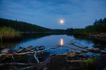 Summer landscape with full moon reflects in a lake at night, Telemark Southern Norway