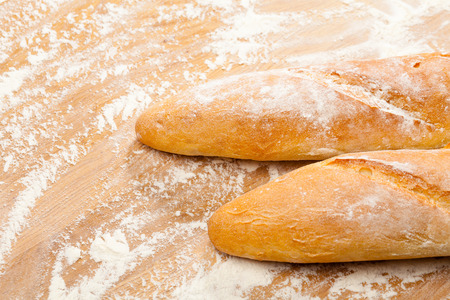 Freshly baked artisanal baguettes  (french bread) on wooden background covered with flour