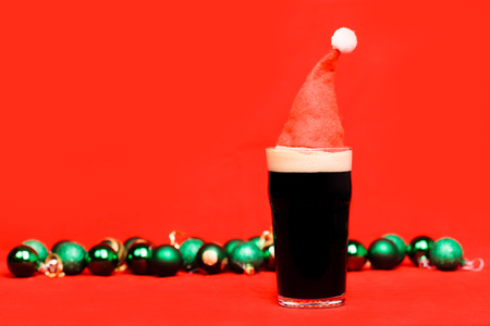 Nonik pint glass of dark beer or stout ale with red santa hat and blurred green christmas baubles in background on red Stock Photo