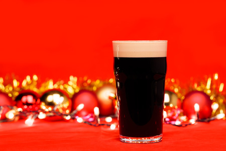 Nonik pint glass of dark beer or stout ale with christmas lights baubles and tinsel on red background Stock Photo