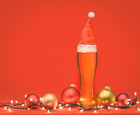 Close-up shot of full pilsner glass of pale lager beer or ale with Santa Claus or christmas red hat, christmas lights and baubles on red background Stock Photo