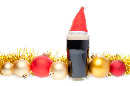 Full pint glass of dark beer or stout ale with Santa Claus or christmas red hat and christmas baubles on white background Standard-Bild - 113610624