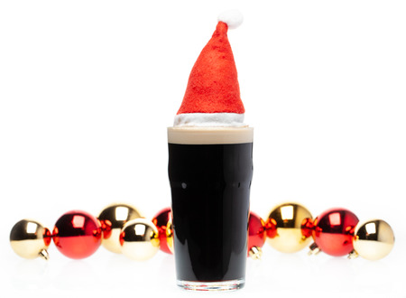 Full pint glass of dark beer or stout ale with Santa Claus or christmas red hat and christmas baubles on white background Standard-Bild - 113610626