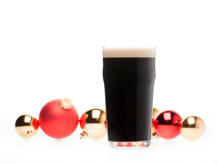 Full pint glass of dark beer or stout ale with blurred christmas baubles in background on white Standard-Bild - 113610752