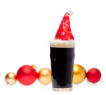 Full pint glass of dark beer or stout ale with Santa Claus or christmas red hat and christmas baubles on white background Standard-Bild - 113610756