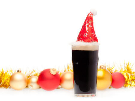 Full pint glass of dark beer or stout ale with Santa Claus or christmas red hat and christmas baubles on white background Standard-Bild - 113610758