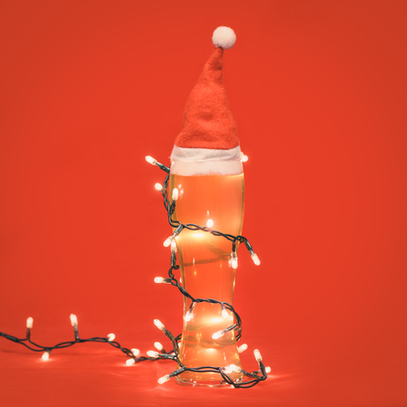 Close-up shot of full pilsner glass of pale lager beer or ale with Santa Claus or christmas red hat on top and wrapped in christmas lights on red background