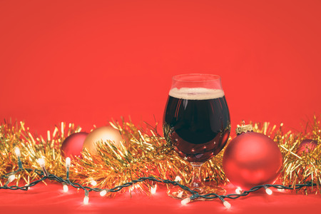 Snifter glass of dark ale or porter beer with  christmas lights baubles and tinsel on red background
